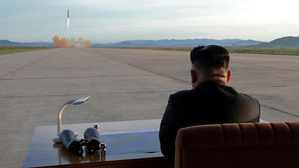 Le leader nord-coréen Kim Jong-un, vu de dos, regarde au loin une fusée décoller.