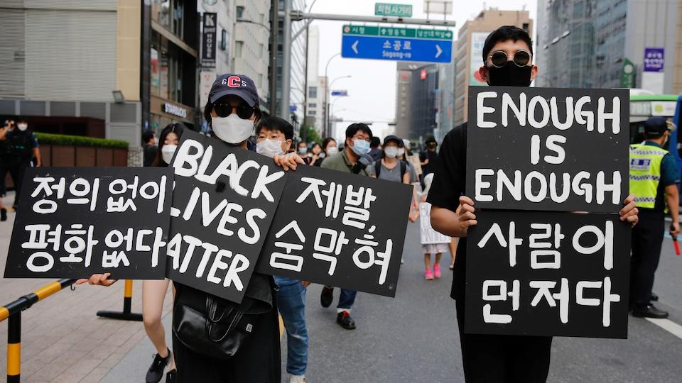 Des gens portant des masques marchent dans la rue en brandissant des pancartes.
