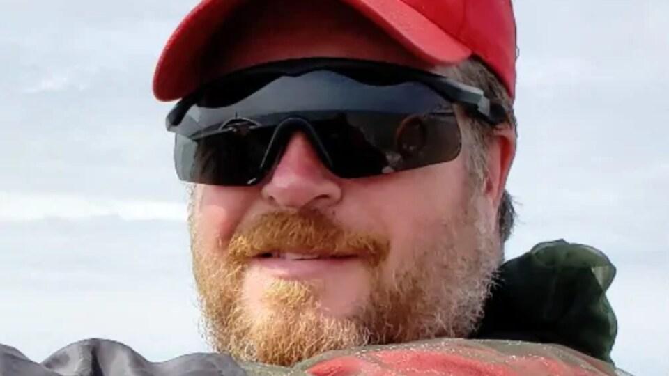 Corey Hurren, portant une casquette et des lunettes de soleil, regarde la caméra.