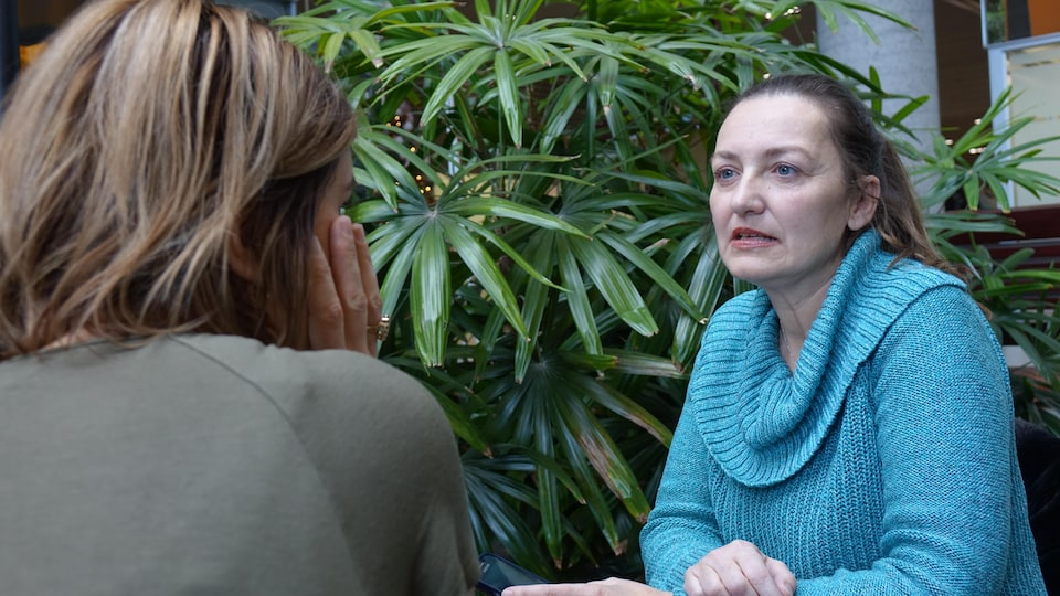 Deux femmes discutent : l'une est de dos et l'autre de face