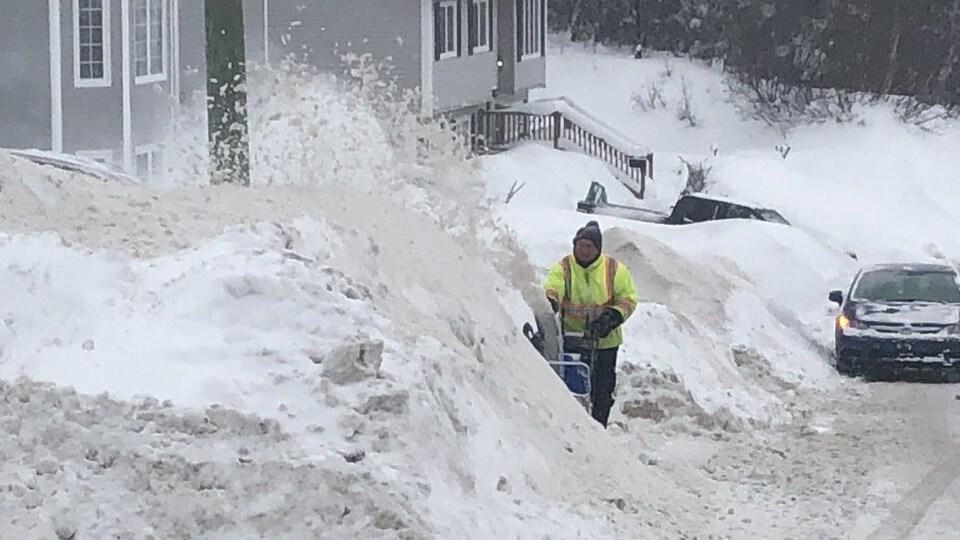 Un homme manie sa souffleuse devant un énorme amoncellement de neige. La neige est plus haute que les voitures garées dans la rue.