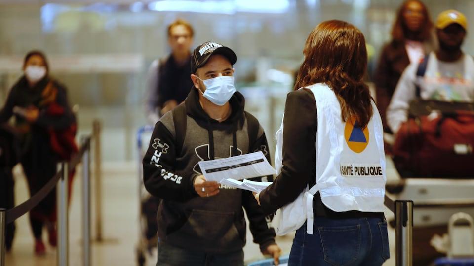Une femme de la santé publique remet des directives écrites à un homme portant un masque.