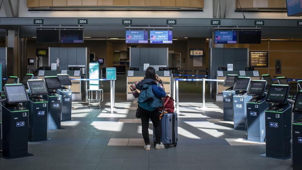 Une femme seule face aux guichets de l'aéroport.