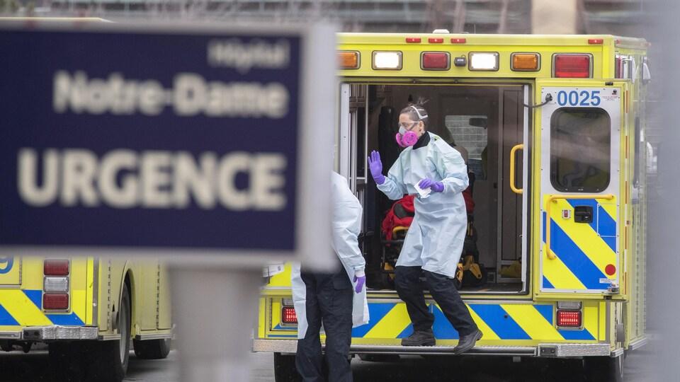 Une femme portant un masque sort d'une ambulance.