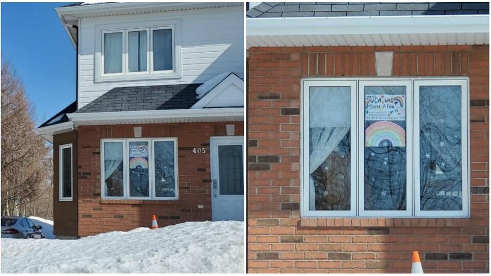 Une maison avec un dessin d'arc-en-ciel accroché dans une fenêtre.