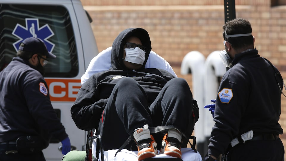Un homme allongé sur une civière porte un masque de protection médical.