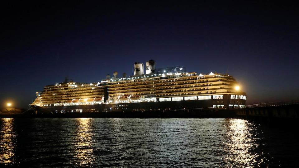 Le bateau illuminé est vu de nuit.