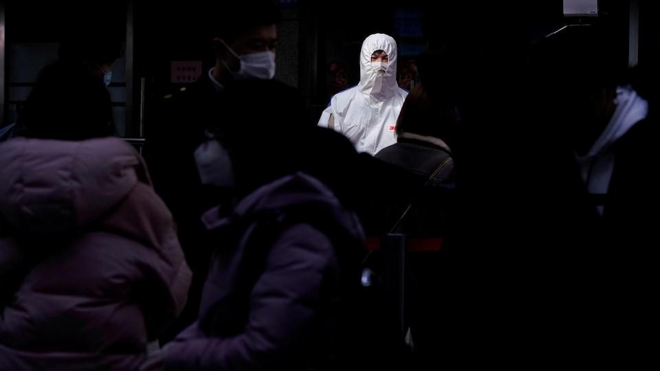 Une personne en uniforme blanc, dont seuls les yeux sont visibles, est au milieu d'autres personnes masquées.