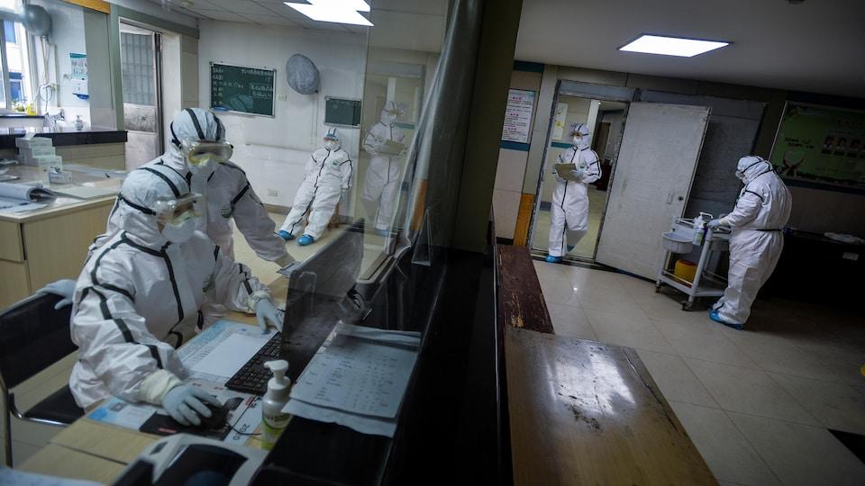 Les travailleurs portent tous des combinaisons de protection, des lunettes et des masques respiratoires.