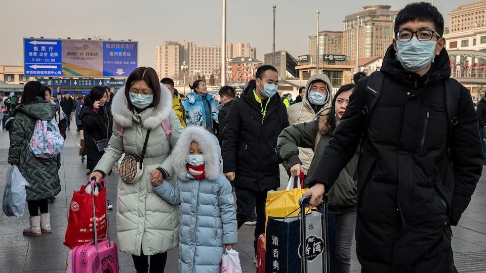 Plusieurs personnes tenant des valises portent de masques respiratoires.