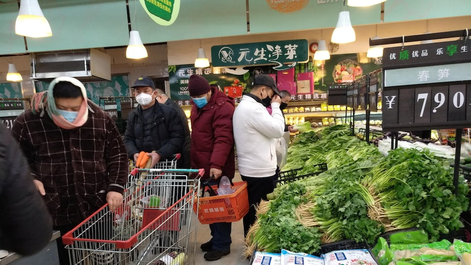 Des hommes portant des masques font la file pour passer à la caisse dans un marché.