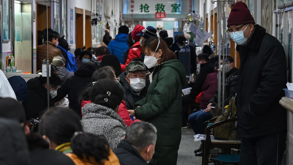 Des dizaines de personnes portant des masques attendent dans un couloir de l'hôpital.
