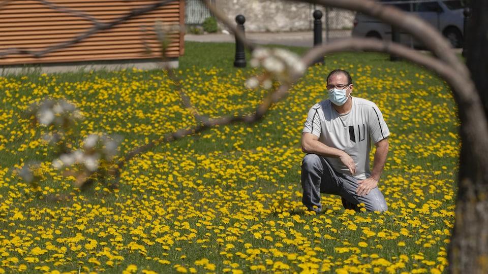 François Poulin, le visage couvert d'un masque, pose dans un terrain couvert de pissenlits.