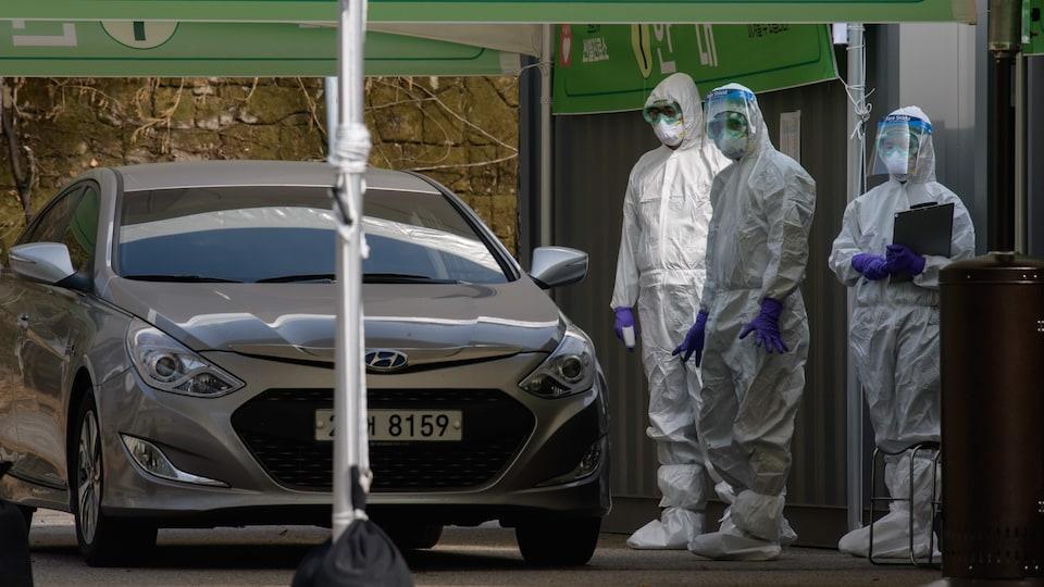 Des travailleurs de la santé portant des combinaisons de protection attendent de contrôler un automobiliste.