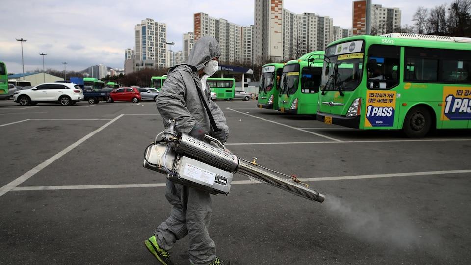 Un homme masqué tient un grand pulvérisateur à la main d'où s'échappe une fumée. Il se trouve dans un stationnement, en Corée du Sud.