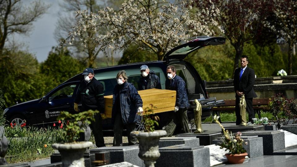 Une femme et trois hommes portent un cercueil dans un cimetière. Ils portent tous des masques.