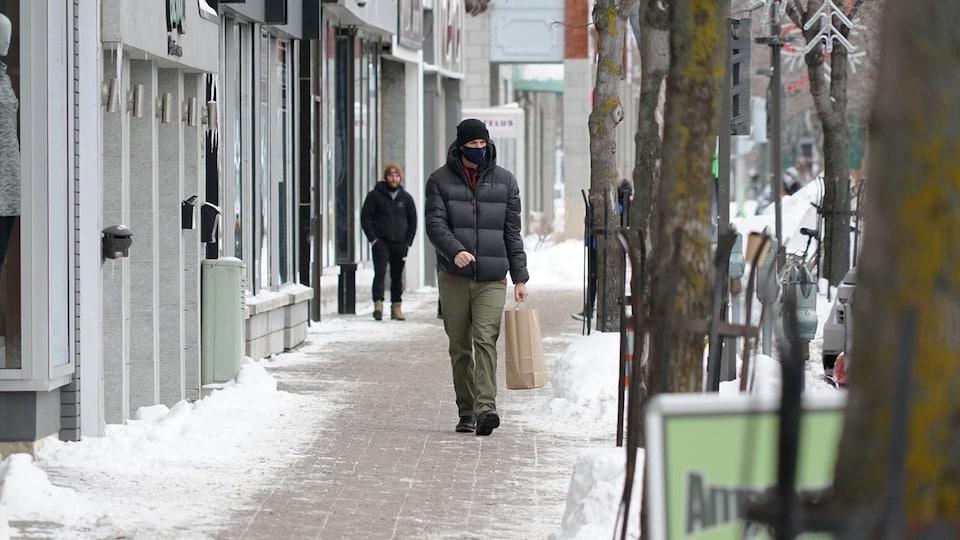 Un homme qui porte un couvre-visage déambule sur la rue Saint-Germain à Rimouski.