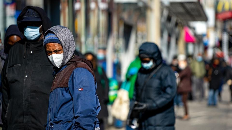 Des personnes portant un masque attendent en file sur un trottoir.