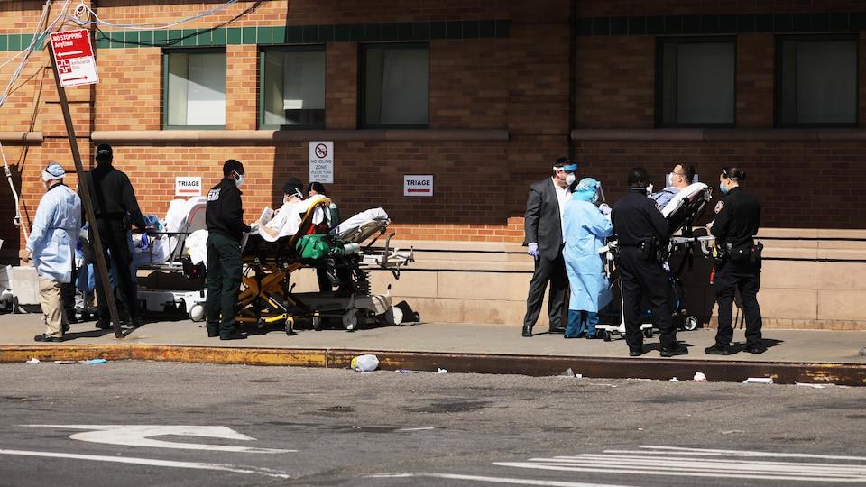 Des lits d'hôpital se trouvent sur un trottoir, des patients s'y font traiter par du personnel en habit de protection.