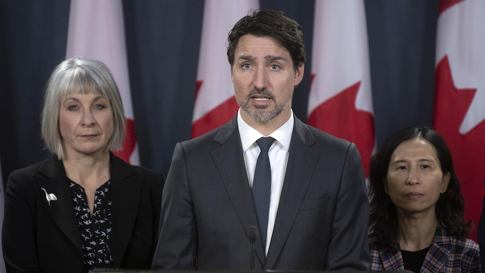 Au centre, se tient Justin Trudeau. À gauche, la ministre de la Santé, Patty Hajdu, et à droite, l'administratrice en chef de la santé publique du Canada, la Dre Theresa Tam.