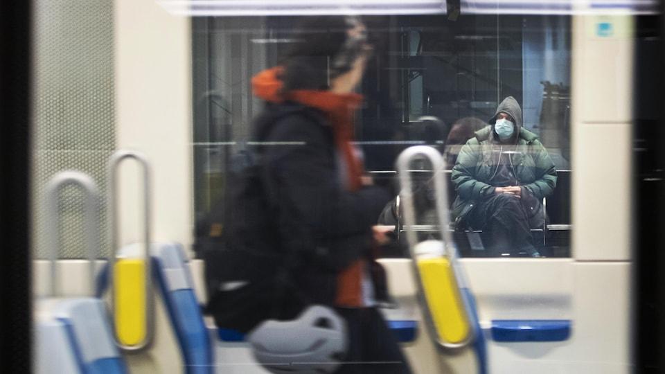 Un homme porte un masque en attendant le métro.
