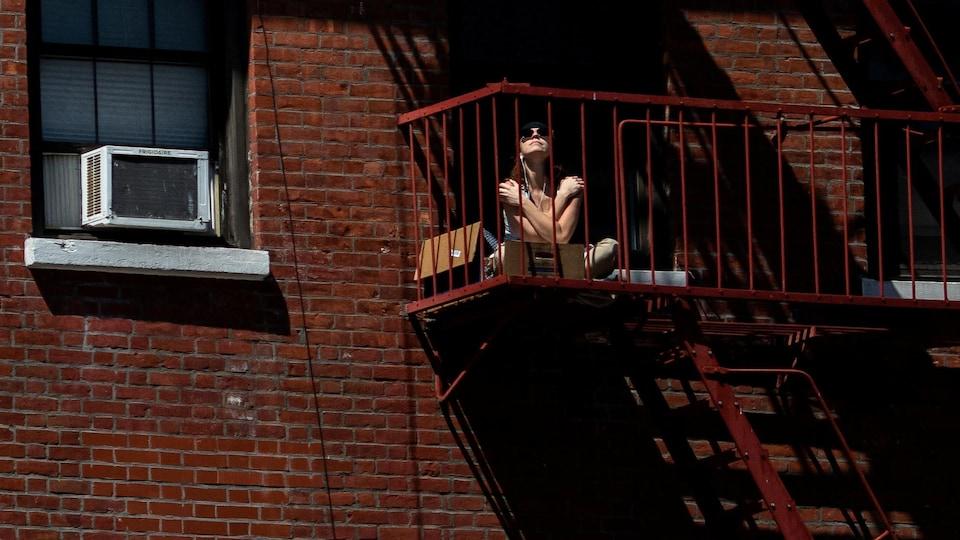 La femme est assise en indien sur un petit balcon en fer, les bras croisés sur la poitrine.