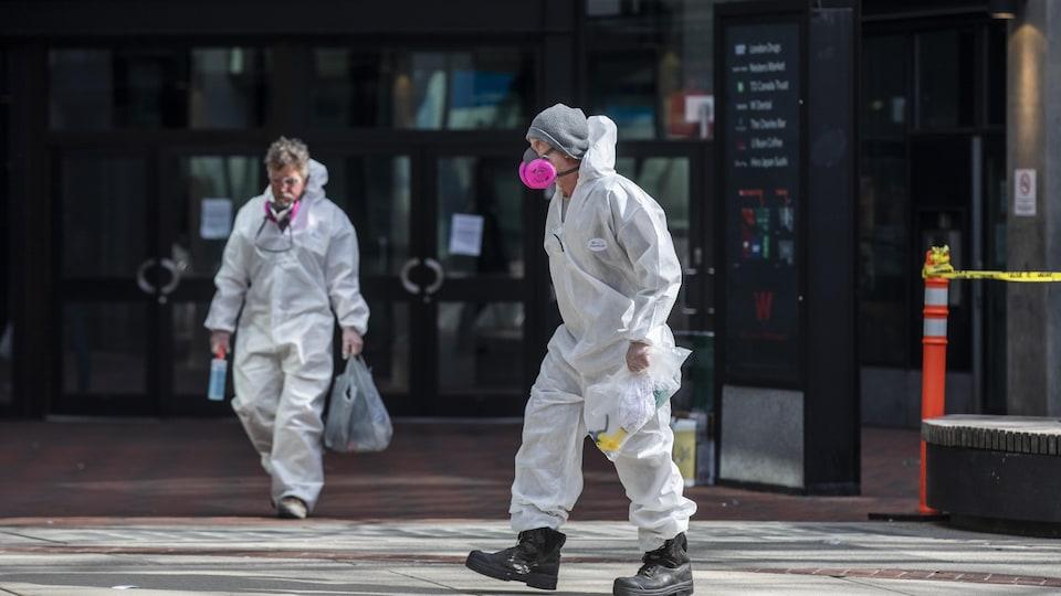 Des personnes en tenue de protection travaillent dans le quartier Downtown Eastside, à Vancouver.