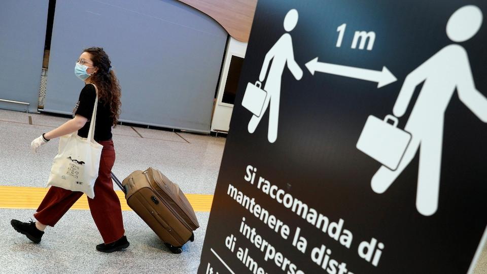 Une femme portant un masque et des gants marche avec une valise.