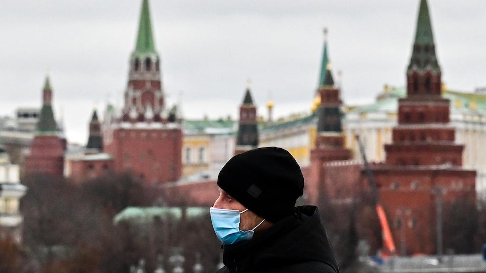 Un homme portant un masque marche sur un pont près du Kremlin.
