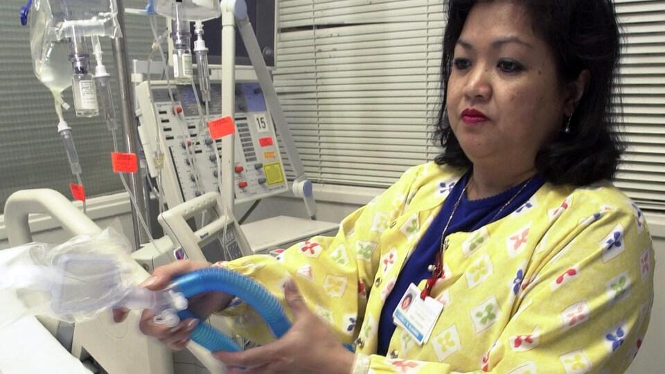 Une infirmière manipule des tubes attachés à un respirateur artificiel.