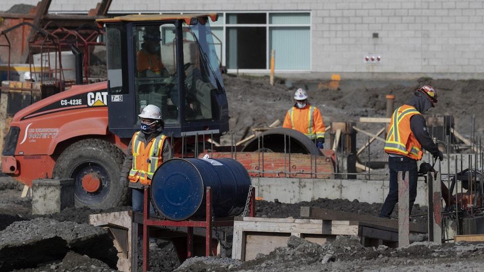 Des travailleurs portant un masque travaillent sur un chantier de construction.
