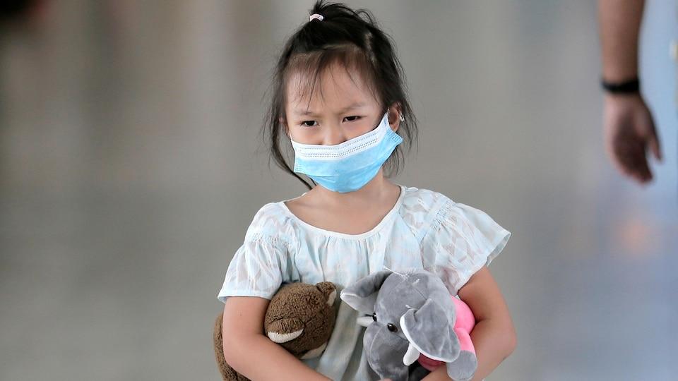 Une fillette portant un masque transporte deux animaux en peluche.