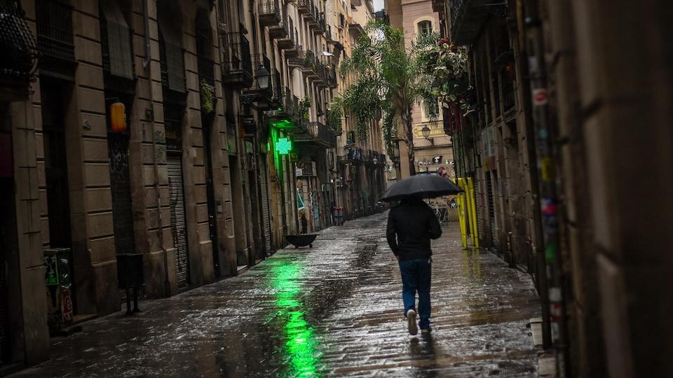 Un homme marche sous la pluie dans une petite rue de Barcelone.