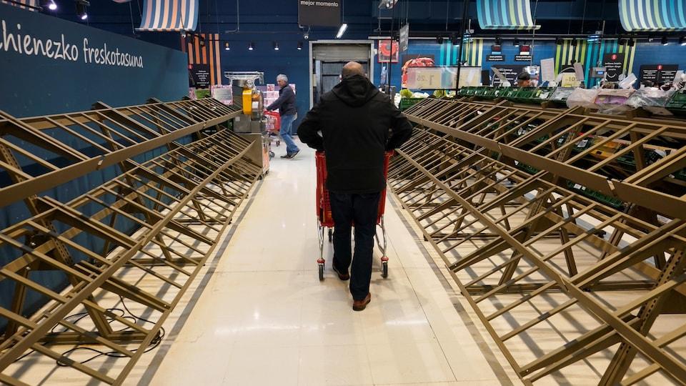Un homme passe devant des étagères vides dans un supermarché, dans la ville basque de Guernica, en Espagne, le 13 mars 2020.