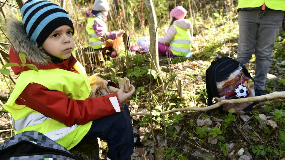 Un garçon mange un sandwich dans un boisé. D'autres élèves mangent aussi un peu plus loin..