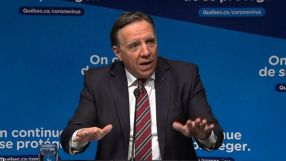 Prime Minister Legault gesticulates at a press conference.