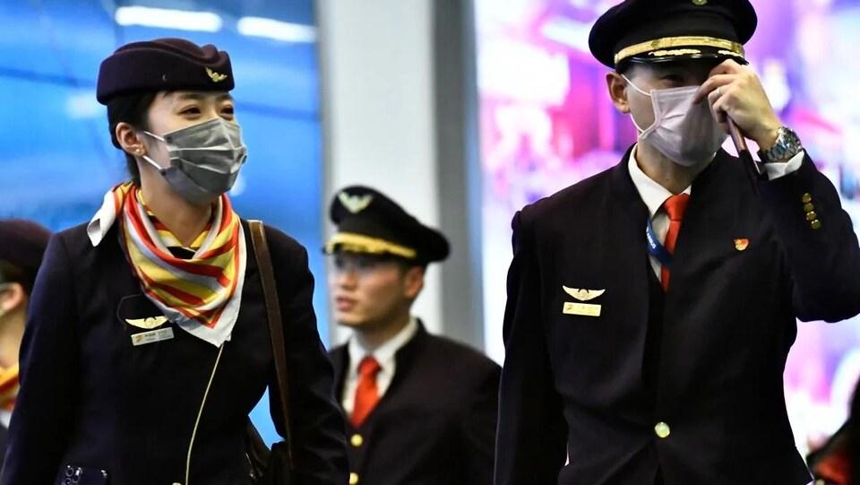 Des pilotes chinois portent des masques recouvrant leur bouche et leur nez.