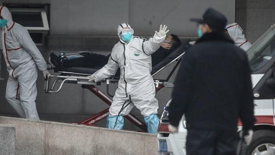 Des ambulanciers transportent un homme en civière.