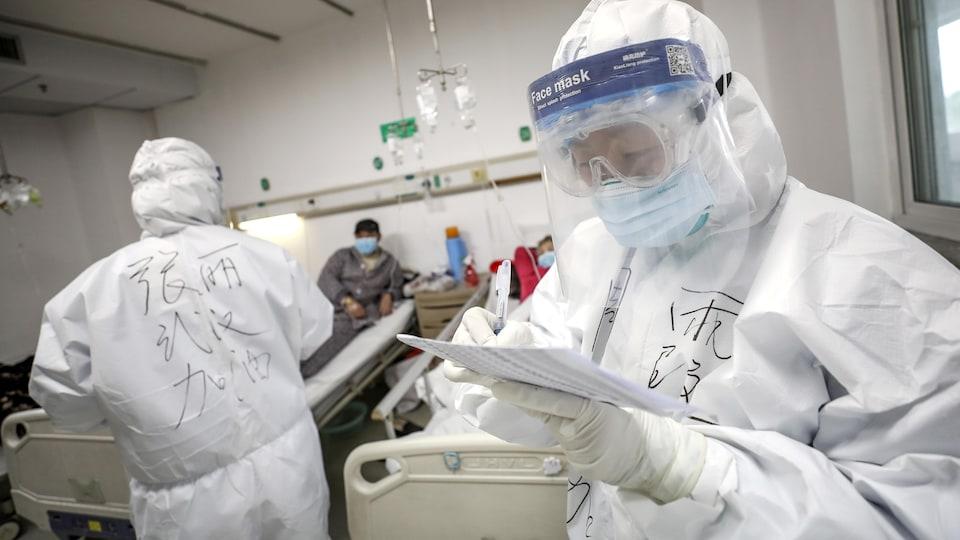 Deux employés vêtus de combinaison de protection sont dans un hôpital avec deux patients.
