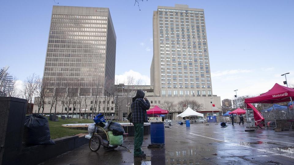 Une personne itinérante au cœur de la place Émilie-Gamelin face à l'hôtel de la Place Dupuis, au centre-ville de Montréal.