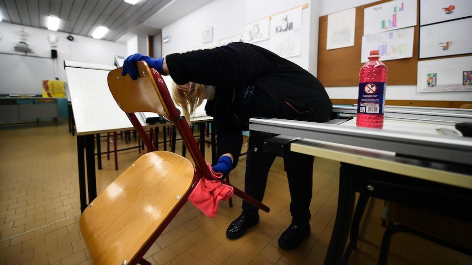 Une femme portant des gants nettoie les pieds d'une chaise dans une salle de classe.