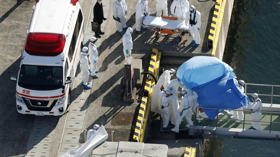 Plusieurs travailleurs de la santé munis d'équipements de protection escortent un passager protégé par un drap bleu sur une passerelle le menant à une ambulance.