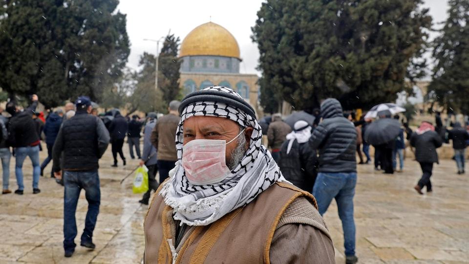 Un Palestinien porte un masque. Le dôme du Rocher se profile derrière lui.
