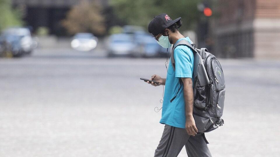 Un homme portant un masque marche dans une rue en regardant son téléphone cellulaire.