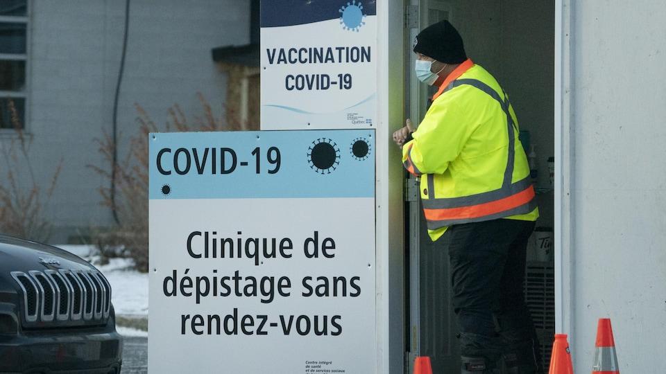 Un préposé attend près d'une affiche qui indique l'emplacement d'une clinique de dépistage.