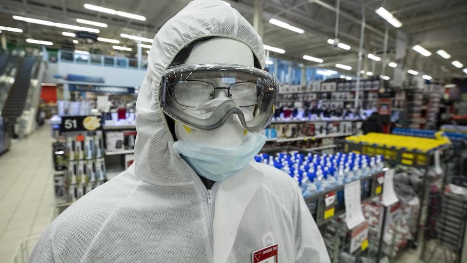 Un uniforme blanc , un masque et des lunettes de protection sont disposés sur un mannequin dans un magasin.