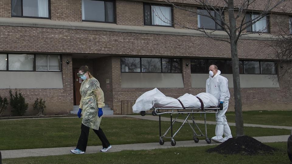 Un travailleur portant une tunique et un masque protecteurs transporte un cadavre sur une civière.