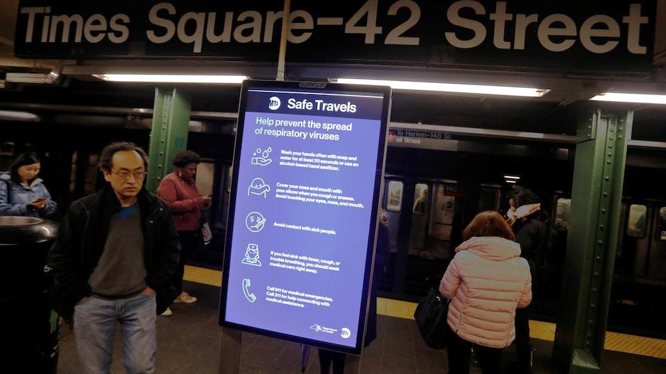 Des passagers du métro passent près d'une affiche indiquant quoi faire pour éviter de contracter la maladie.