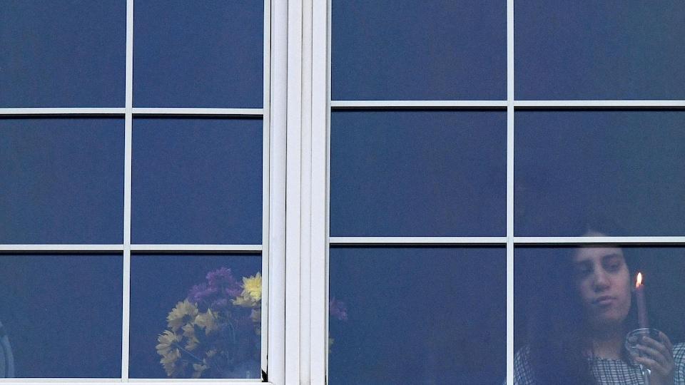 Une jeune femme tient une chandelle devant sa fenêtre lors de la fête orthodoxe de Pâques.