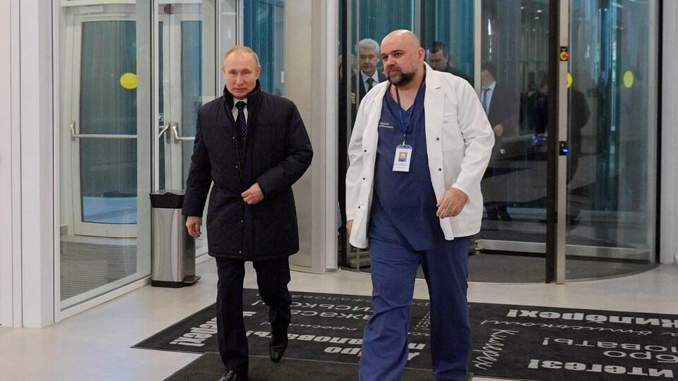 Vladimir Poutine entre dans un hôpital accompagné par le Dr Denis Protsenko.